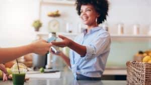 nainen ojentaa maksukorttia kassahenkilölle